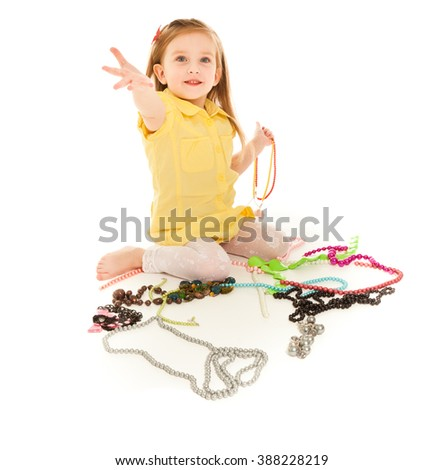 Little girl with a lot of jewel laughing isolated on white - stock photo