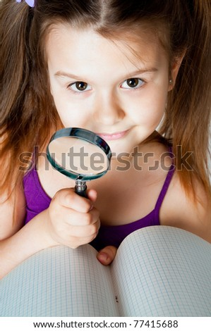 little girl with a magnifying glass on a white background - stock photo