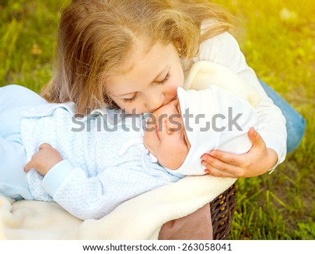 little girl with a newborn brother in the park. soft light - stock photo