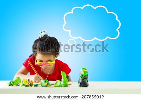 Little girl with a pencil thinking and writing something on table. White cloud at the top of the photo for your text - stock photo