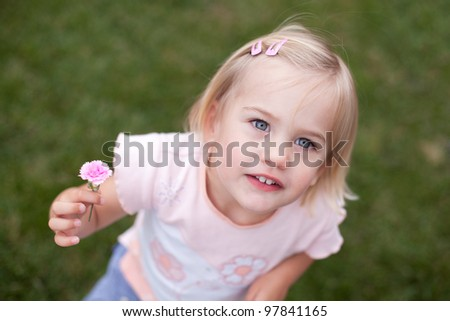 Little girl with a pink flower - stock photo