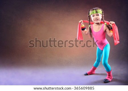 Little girl with a rubber strap at fitness exercise
