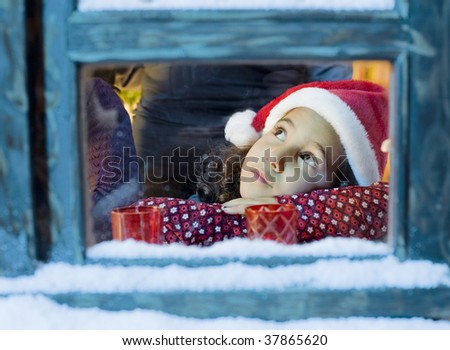 Little girl with a Santa hat  looking outside - stock photo