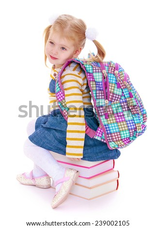 Little girl with a satchel on his shoulders sits on textbooks. Studio photo, isolated on white background. - stock photo