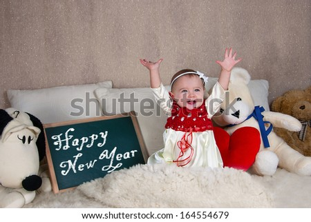 Little girl with a sign with the words Happy New Year. - stock photo