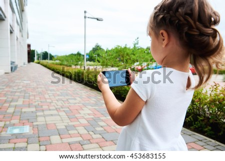 Little girl with a smartphone outdoors