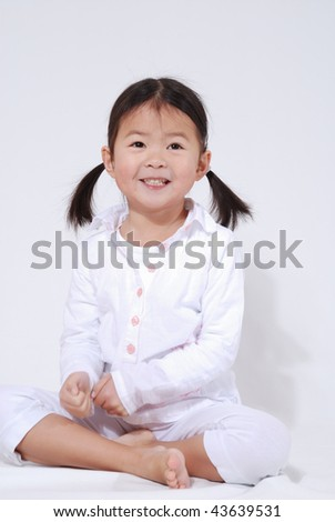 little girl with a smile dressed in white - stock photo