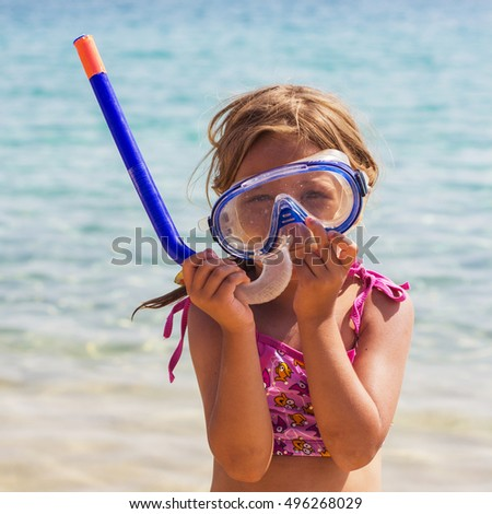 Little Girl with a snorkel scuba mask on the sand beach. Summer portrait of child on vacation.