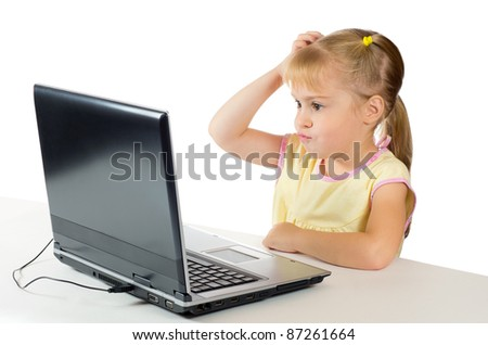 Little girl with a surprised face is on the computer - stock photo