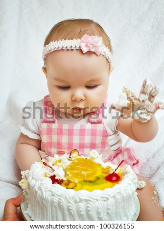 Little girl with a sweet cake in his hands - stock photo