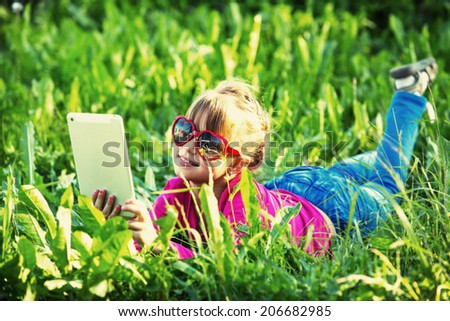 Little girl with a tablet PC lying in the grass on park (film style photography) - stock photo