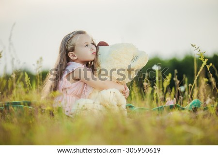 little girl with a teddy bear on nature - stock photo