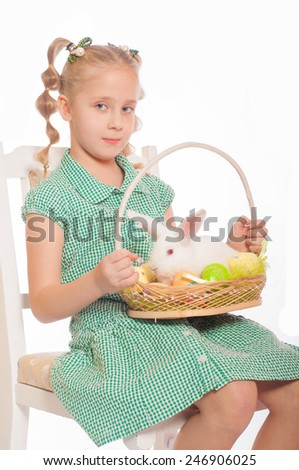 little girl with a white rabbit in a basket easter eggs - stock photo