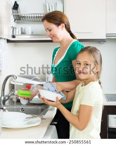 little girl with a woman washing plates in the kitchen after dinner - stock photo