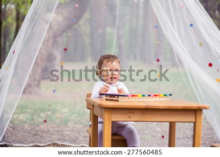 little girl with a xylophone, a table in the woods