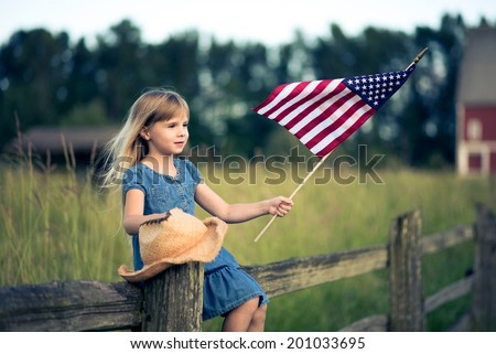 Little girl with American flag sitting on the fence. - stock photo