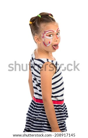 Little girl with an abstract paint on her face looking over her shoulder and showing her tongue, isolated - stock photo