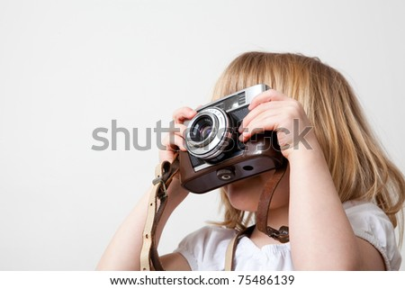 Little girl with an old camera. Studio shot. - stock photo
