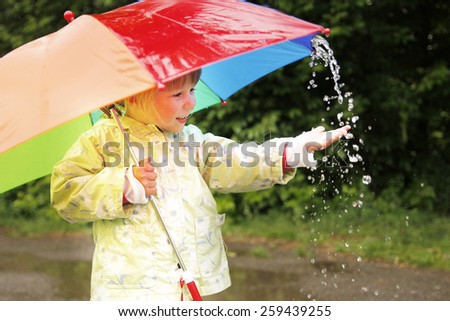 little girl with an umbrella in the rain - stock photo