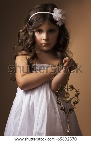 Little girl with antique copper toy. Low key. - stock photo