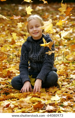 Little girl with autumn leaves falling around her - stock photo
