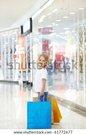 Little girl with bags in the store - stock photo