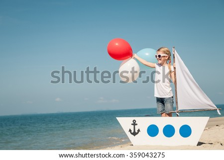 little girl with balloons standing on the beach at the day time. Concept of happy youth.