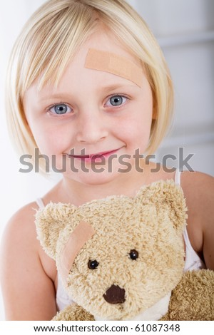 Little girl with band-aid on her face holding a teddy bear