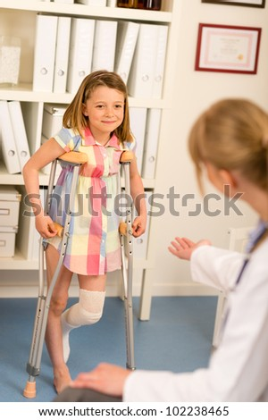 Little girl with bandaged leg standing with crutches surgery office - stock photo