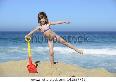 Little girl with beach toy shovel on vacation smiling