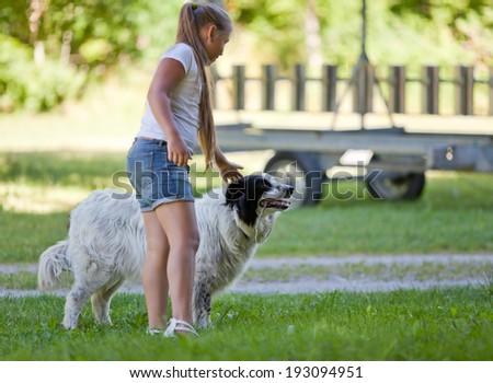 Little girl with best friend in summer garden - stock photo