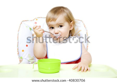 Little girl with bib sitting in baby chair and eating with spoon
