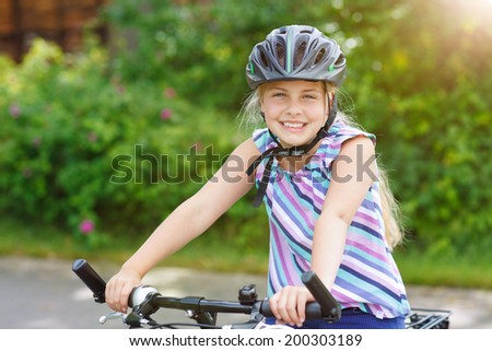 little girl with bicycle smiling - stock photo
