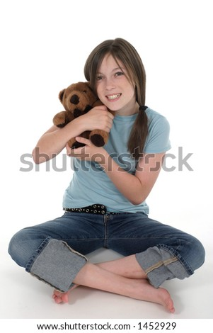 Little girl with big, cheshire cat grin, smiling and sitting on floor holding a teddy bear.  Shot on white.