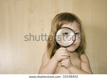 little girl with big magnifier look for something - stock photo