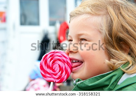 little girl with big round lollipop is smiling - stock photo