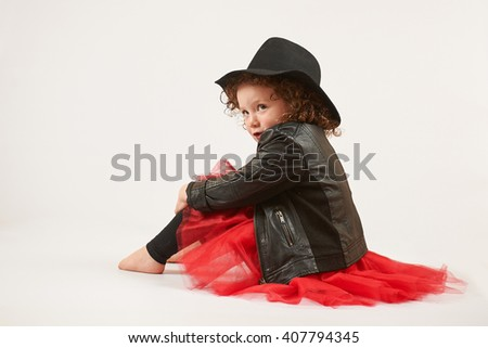 Little girl with black hat sitting and pouting. side view - stock photo