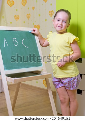 Little girl with blackboard at home - stock photo