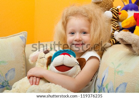 Little girl with blond hair is smiling and playing