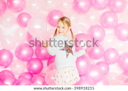 little girl with blond hair playing with pink and beige balloons - stock photo