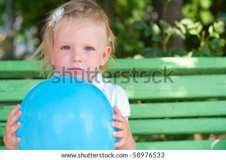 Little girl with blue air balloon sitting o bench - stock photo