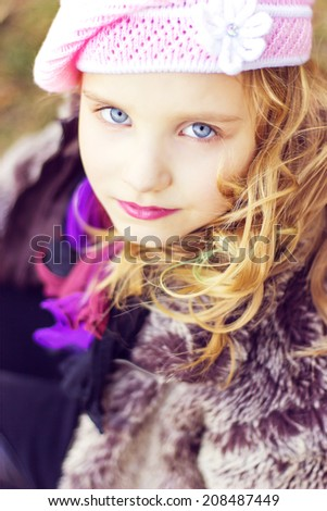 little girl with blue eyes in the pink hat sitting in the forest