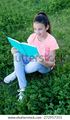 Little girl with blue eyes reading a book at the garden - stock photo