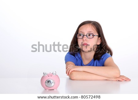 Little girl with bored look sitting by piggybank - stock photo