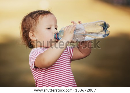 little girl with bottle of mineral water - stock photo