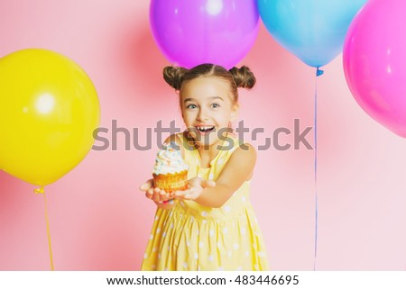Little girl with bright balloons and a cake on a pink background