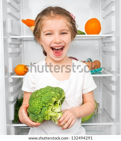 little girl with broccoli against a refrigerator with food - stock photo
