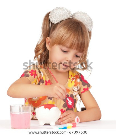 Little girl with brushes painting piggy bank. Isolated on white background. - stock photo
