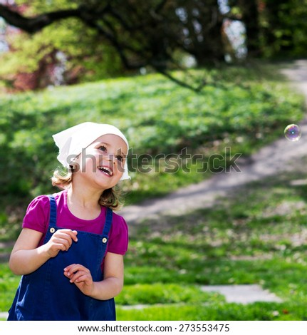 Little girl with bubbles on the summer garden - stock photo