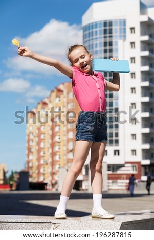Little girl with candy lollipops on city background